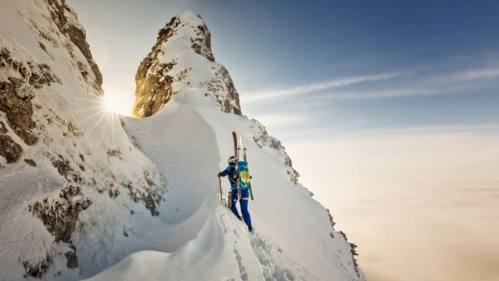 Climber scales snowy peak with skis in a backpack
