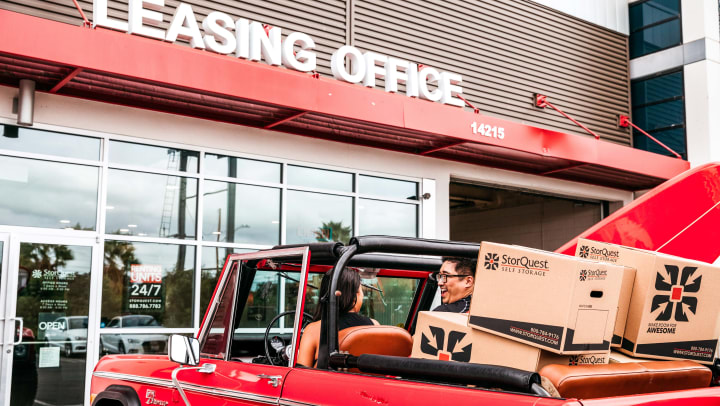 A woman and man sitting in a red jeep filled with moving boxes in a parking lot for a building that says leasing office on it