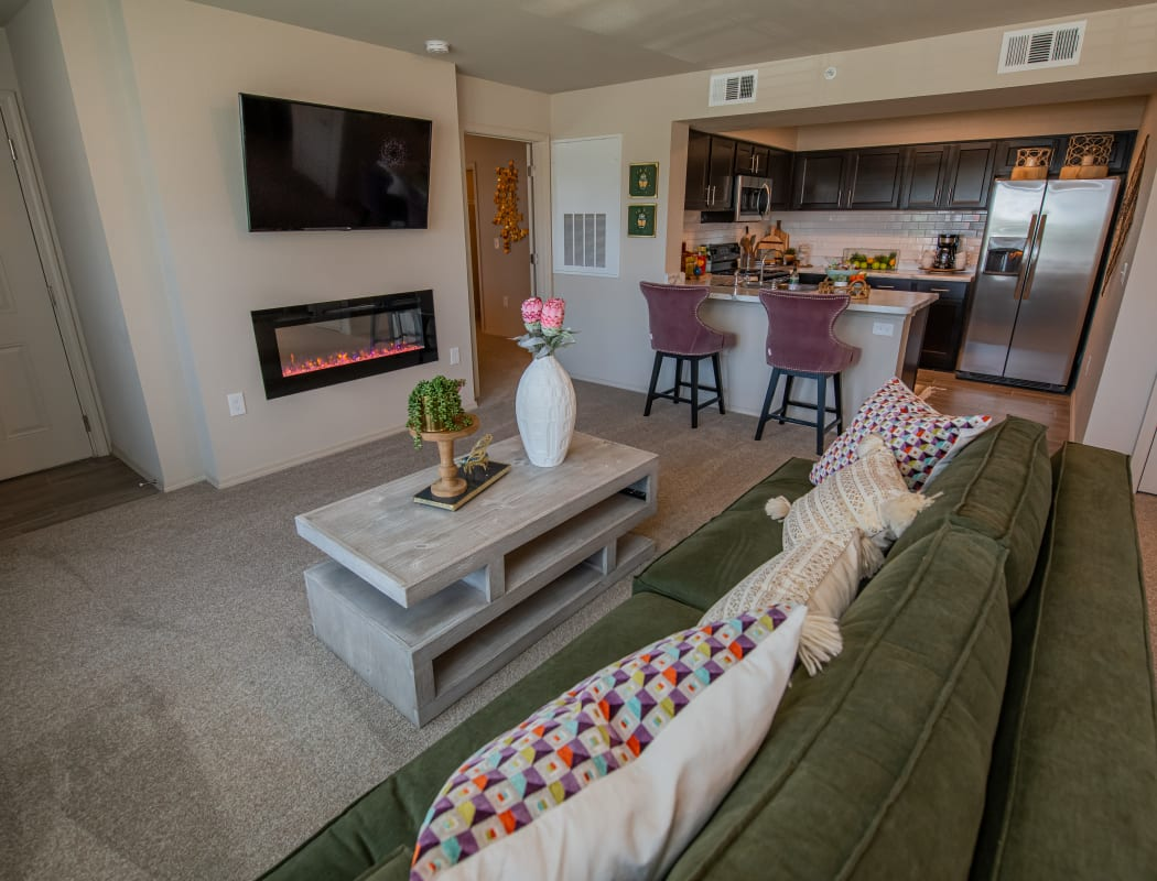 Open living room with LED fireplace and kitchen at Cottages at Crestview in Wichita, Kansas