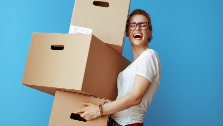 Woman smiling and holding a pile of cardboard boxes.