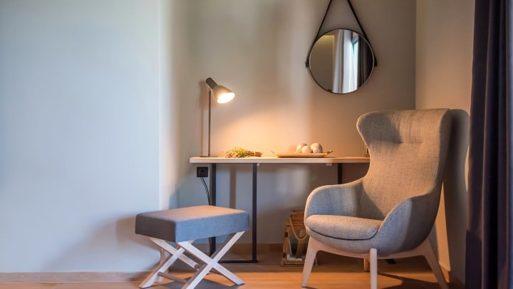 Modern interior of gray room with wingback armchair. Background with table, lamp, and mirror.