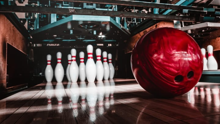 Red bowling ball in front of a set of ten bowling pins on a bowling alley lane.