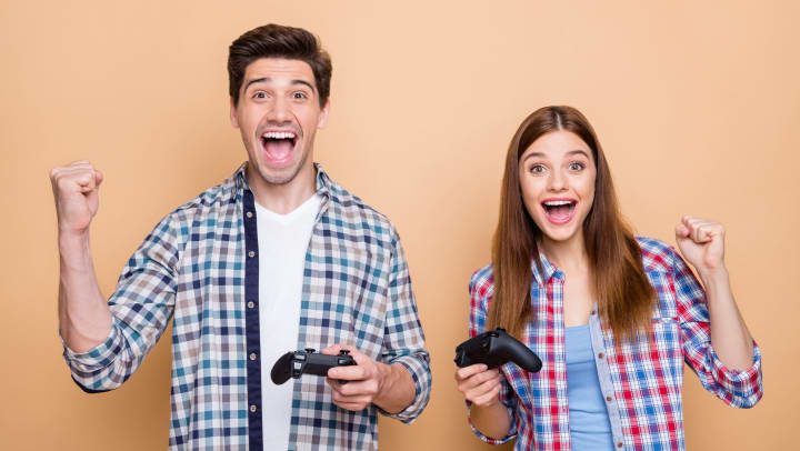 Couple cheering while playing with a PS5 gaming system