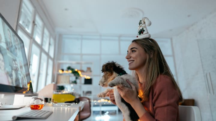 Woman sitting at a computer holding a puppy and wearing a festive holiday hat on her head while smiling.