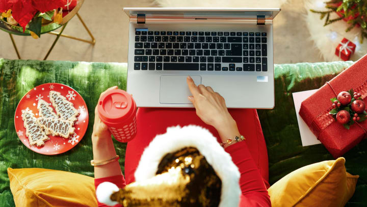 Top view of a person on a laptop, surrounded by holiday decor.