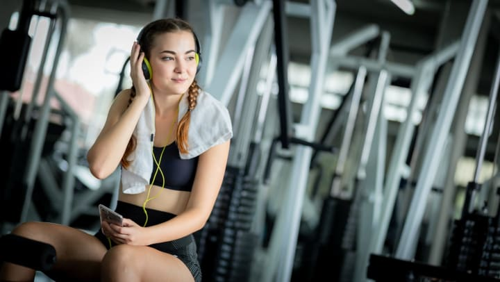 Seated young woman in a gym wearing headphones and smiling