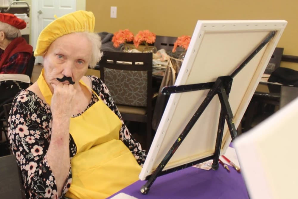 A resident wearing a fake mustache in a painting class at Autumn Grove Cottage at Copperfield in Houston, Texas