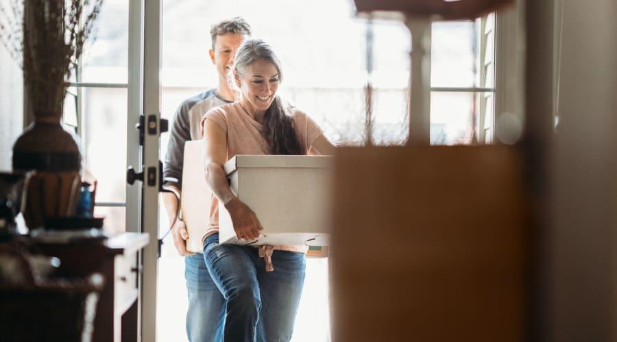 A man and woman carrying boxes into a home near KO Storage of Bemidji in Bemidji, Minnesota