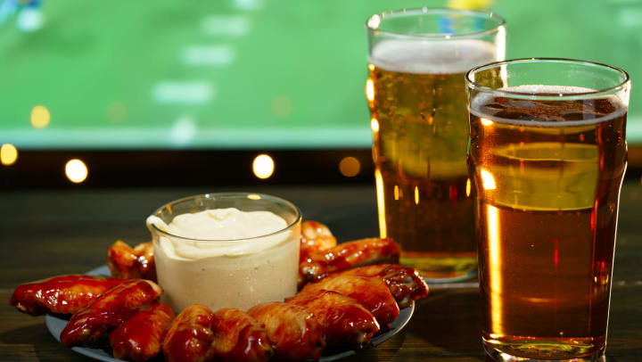 Plate of chicken wings and two beers in front of a sports television