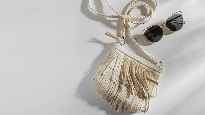 White fringe handbag with sunglasses on a plain white background.