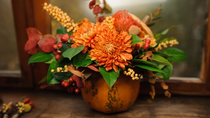 A small pumpkin has been hollowed out from the top to make a natural vase and filled with flowers, berries, and greenery.