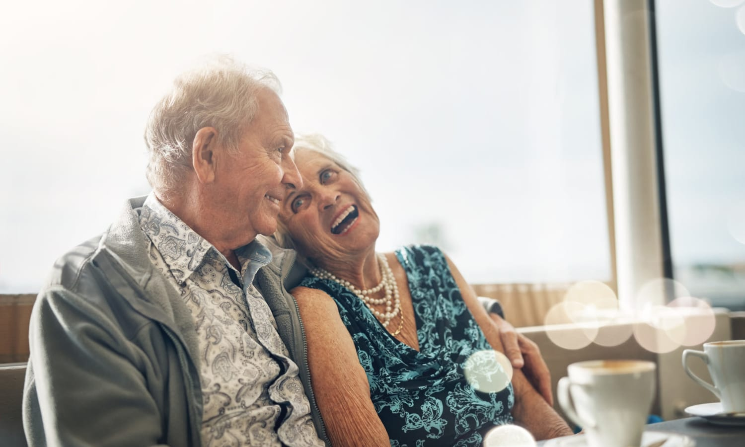 Senior couple laughing and enjoying coffee at Sandpiper Courtyard in Mt. Pleasant, South Carolina