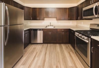Recently renovated kitchen with stainless-steel appliances and dark wood cabinetry in model townhome at Westgate Apartments & Townhomes in Manassas, Virginia