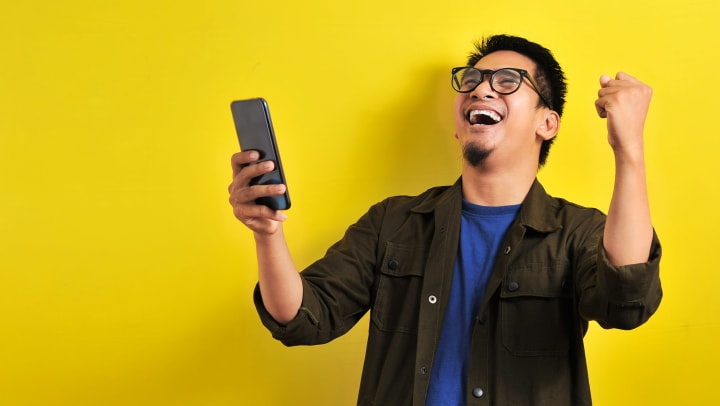 Man pumping his fist in the air and smiling while looking at his cell phone.