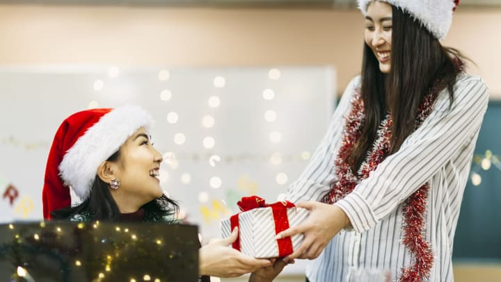 Woman wearing Santa hat hands a gift to another woman wearing a Santa hat