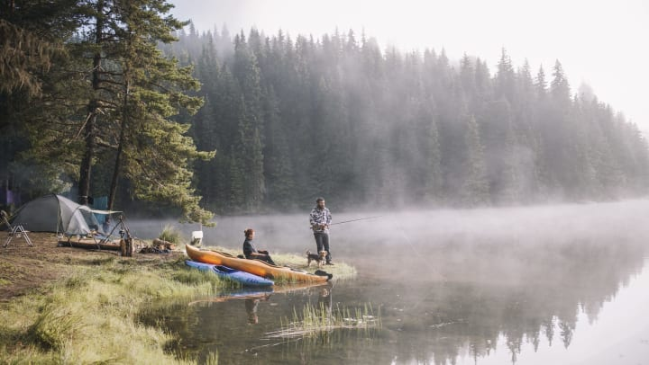 A forest setting next to a foggy lake. Two men and a dog are camping. There is a tent and two canoes. One man is sitting by the lake. The other man is standing and fishing.