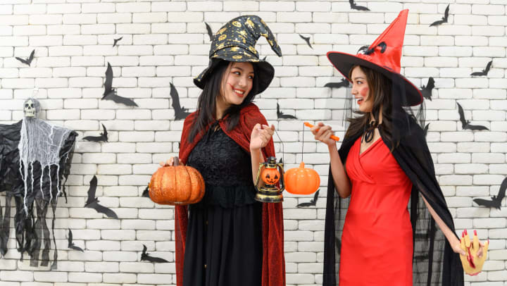 Two young women wearing black and red witch costumes and standing in front of a white brick wall with Halloween decorations