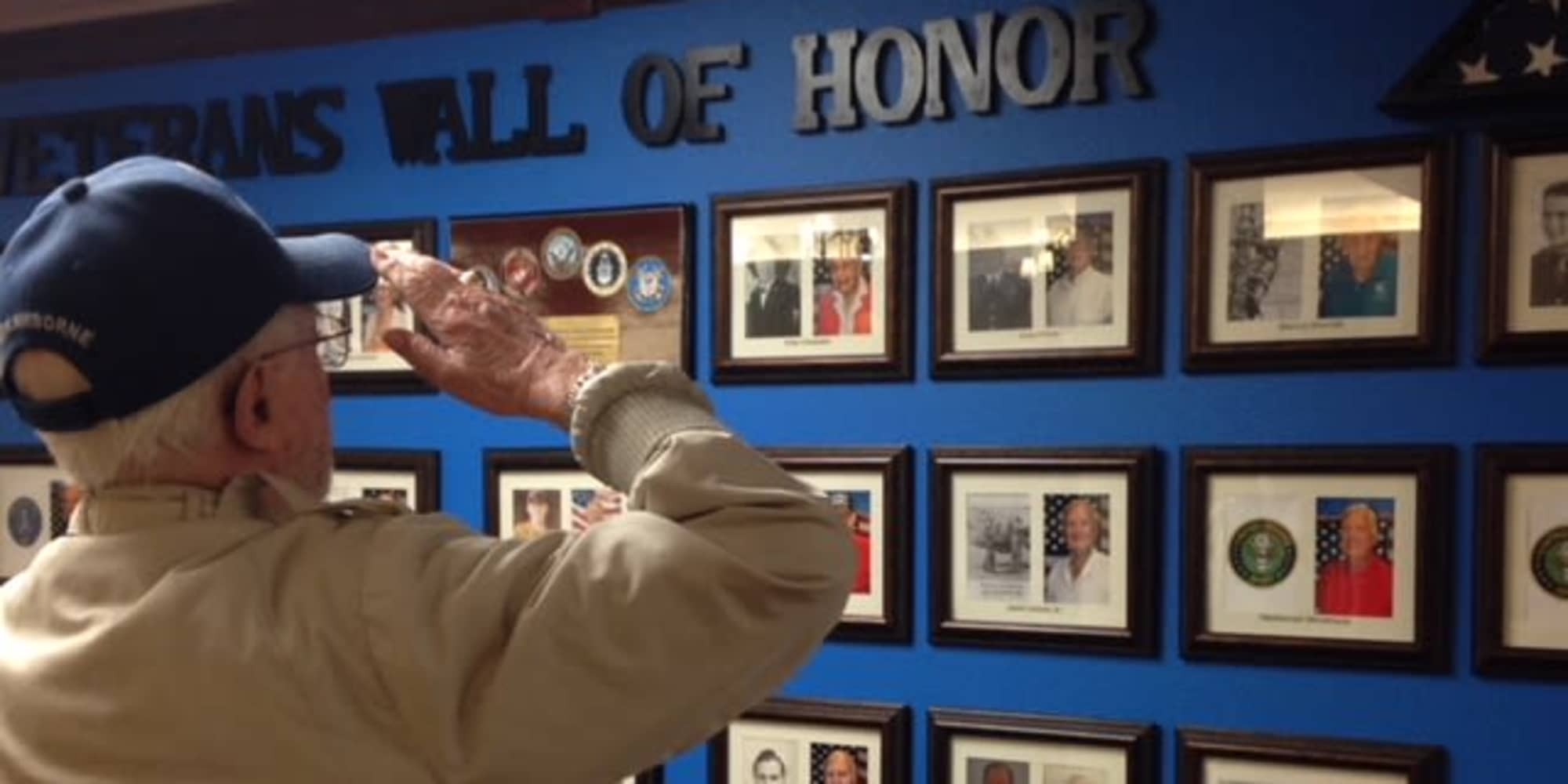 A veteran resident saluting the veterans wall of honor at Magnolia Heights Gracious Retirement Living in Franklin, Massachusetts