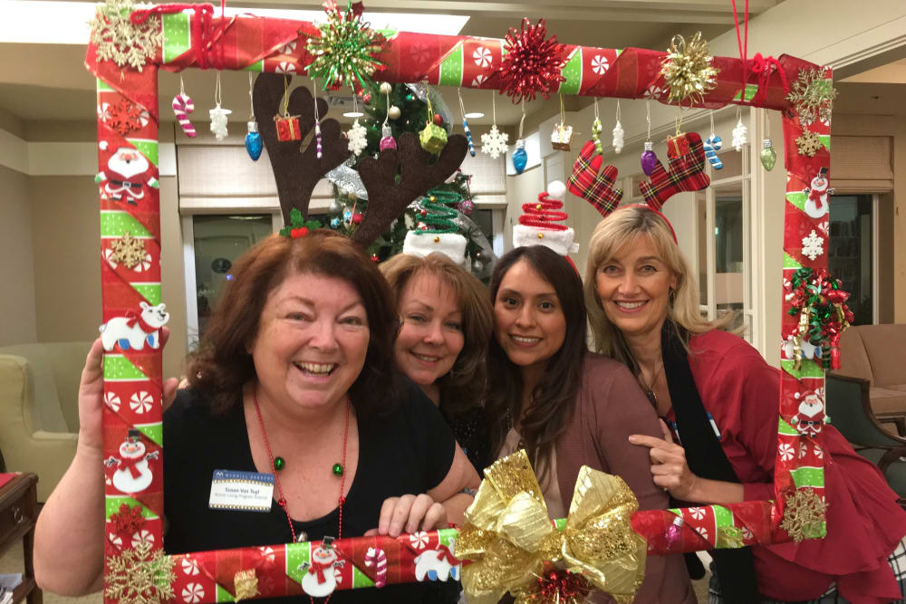 Residents with Christmas frame at holiday party