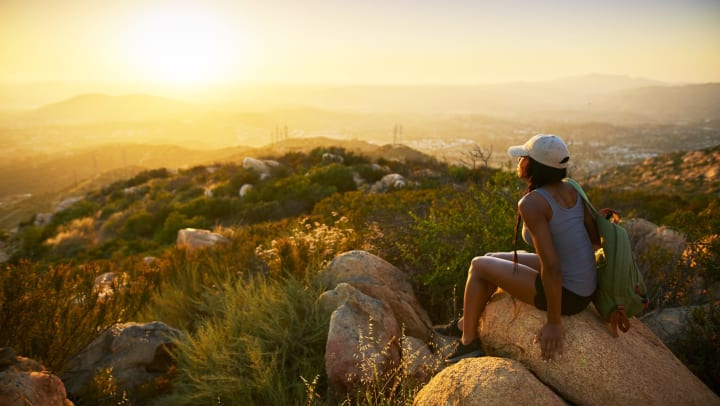Woman looking out over the valley from a large hillside with rocks near Olympus Corsair