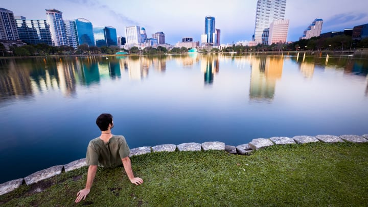Man sitting at the edge of lake in the grass with tall buildings at the the other end of the lake