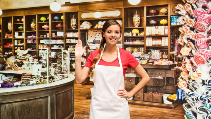 Woman wearing an apron in a candy shop, facing and waving toward the camera.