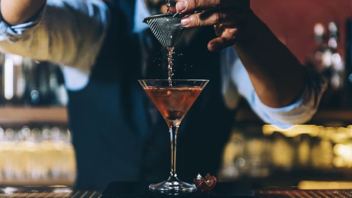 Bartender pouring a cocktail in a blog article on our website at Olympus Boulevard in Frisco, Texas.