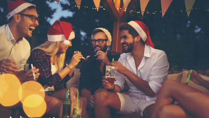 Three laughing men and one woman wearing Santa hats and holding drinks, sit around a table strewn with fairy lights.