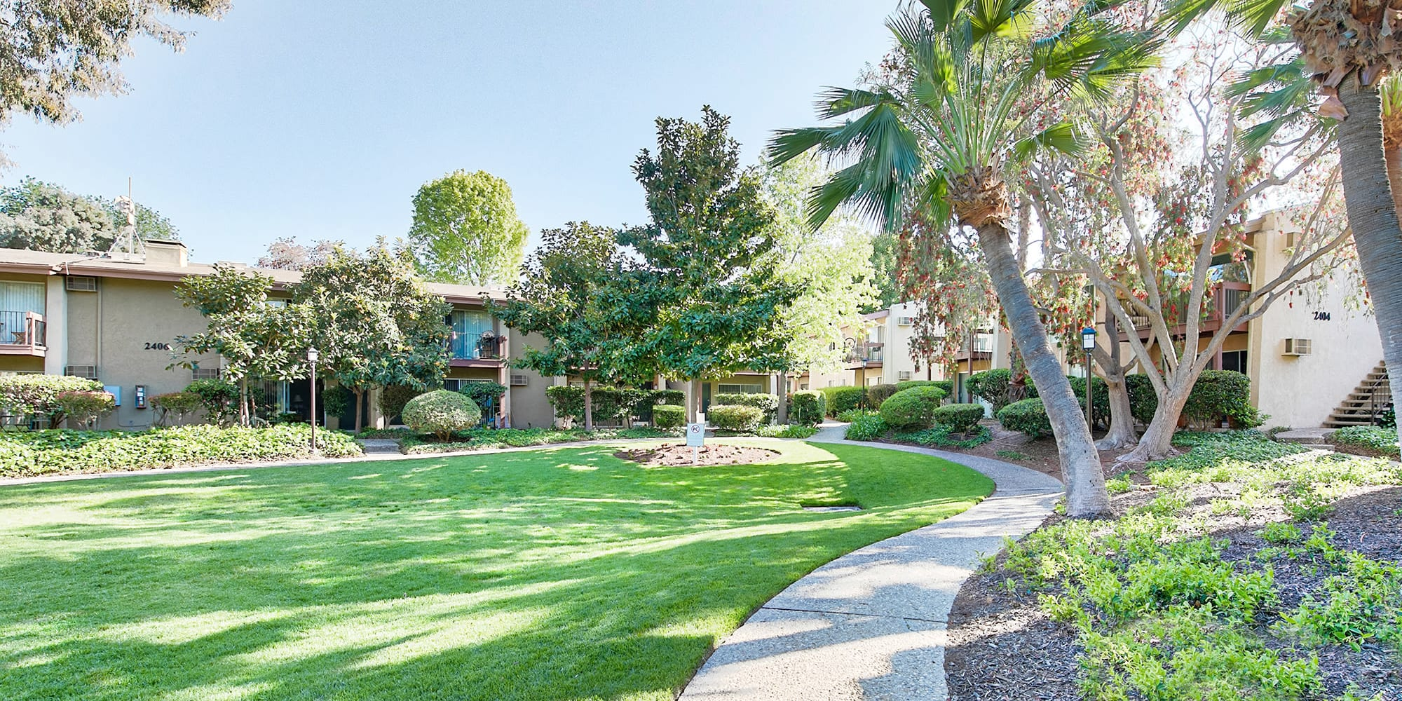 Well-maintained landscaping throughout the community at Mediterranean Village Apartments in Costa Mesa, California