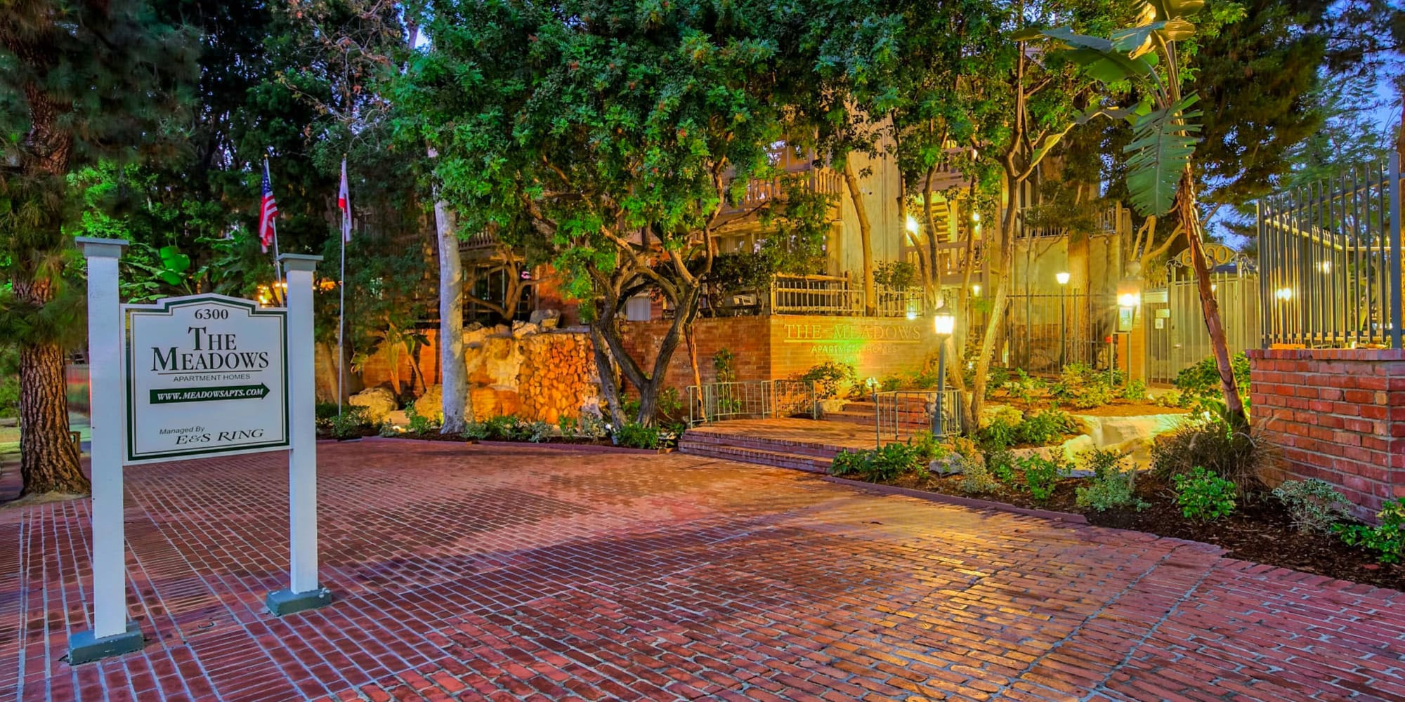 Brick pathway with a welcome sign leading up to one of the resident buildings at The Meadows in Culver City, California