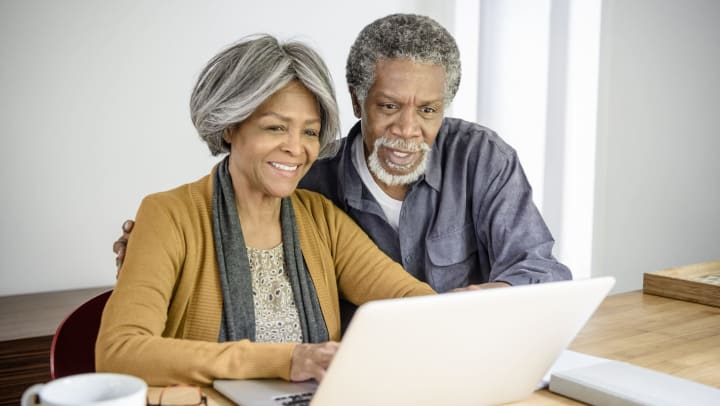 Senior couple looking at laptop together at home. The woman is typing and the man is watching with his arm around her.