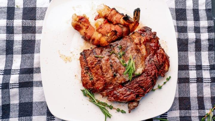 Ribeye steak with jumbo shrimp on a white plate sitting on a plaid linen cloth.