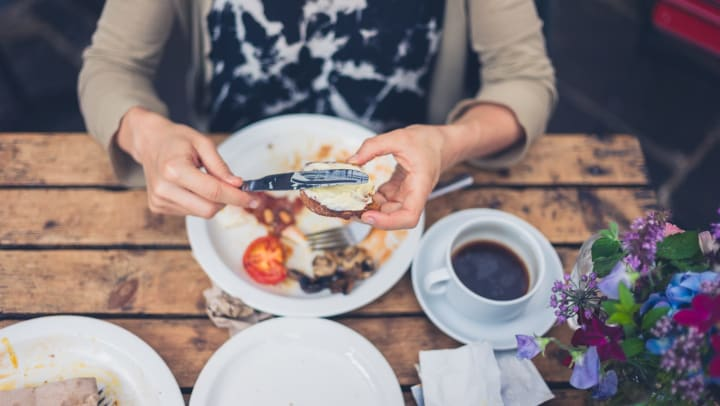 Shot from above of a woman putting a spread on a piece of bread, with her plate and a cup of coffee slightly blurred below.