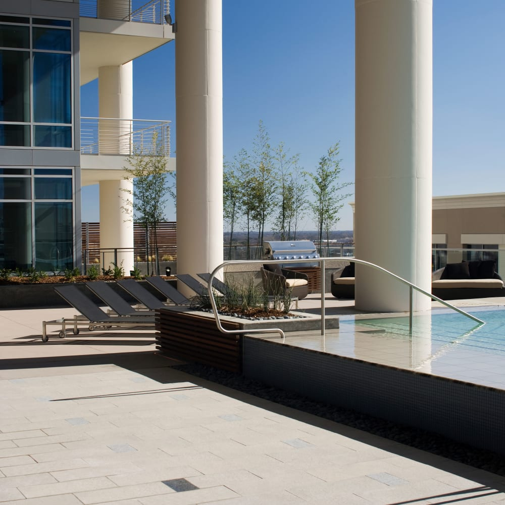 Poolside lounge chairs with BBQ grill at The Heights at Park Lane in Dallas, Texas