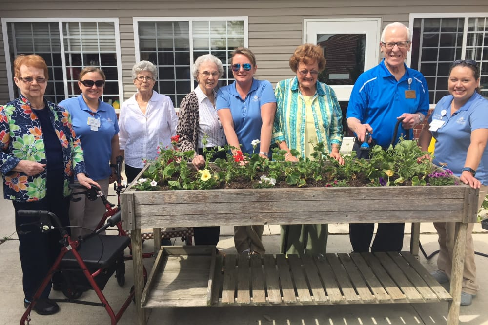 A group of staff and residents around a planter box at Orchard Grove Health Campus in Romeo, Michigan