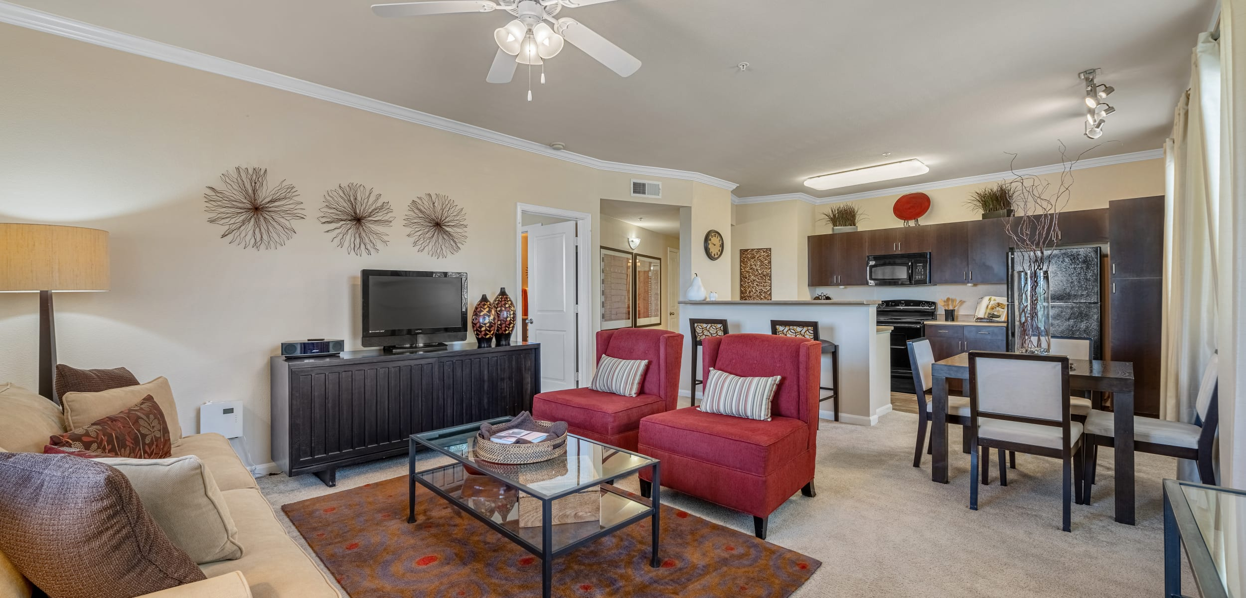 Bright and cheerful living area with carpet and ceiling fan at Marquis at Sonoran Preserve in Phoenix, Arizona