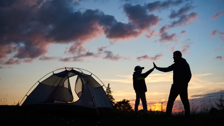 Two silhouetted people high-fiving next to a tent