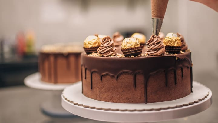 Chocolate cake being decorated with a piping bag.