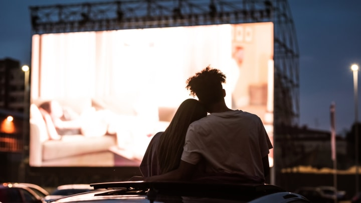 Couple cuddling up on top of a car in front of a drive-in screen.