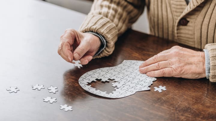 Person sitting at a table working on a puzzle featuring the human head with the brain unfinished.