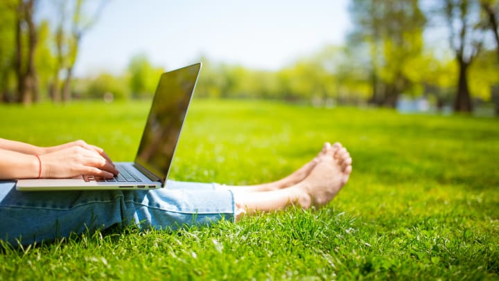 Person sitting on the grass typing on a laptop