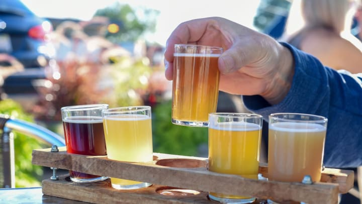 Man outside, lifting a glass of beer out of a tasting tray full of different beers.