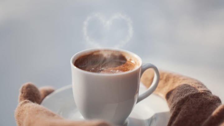 Mittened hands holding a hot cup of coffee with a heart above it, seemingly formed from the steam.