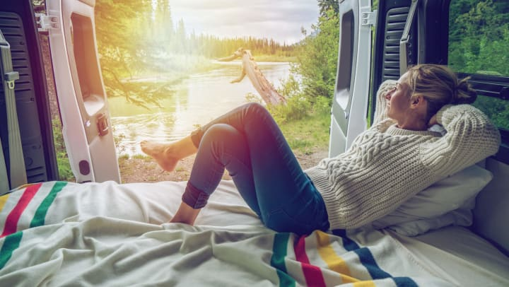 Woman lying in bed inside camper van, with back doors open and a view of nature in the background