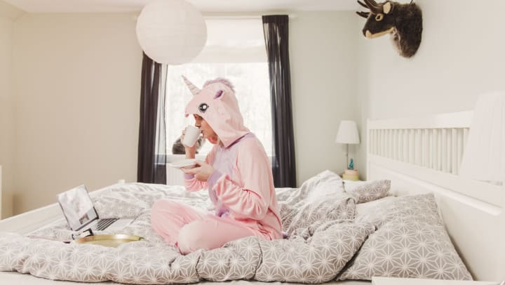 Woman in a unicorn costume sitting on bed, sipping from a mug, with a laptop open in front of her.