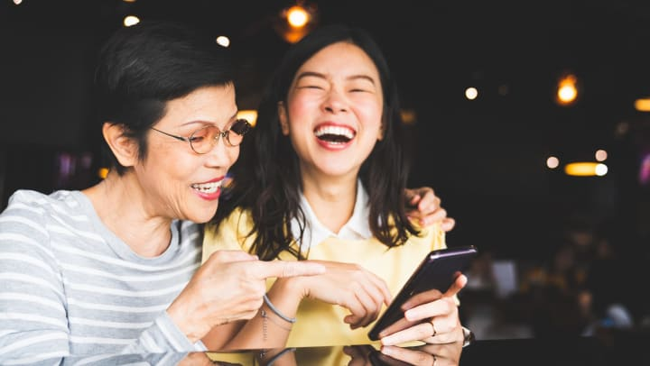 An older woman and a younger woman sitting together in a dark interior and smiling while looking at a smartphone