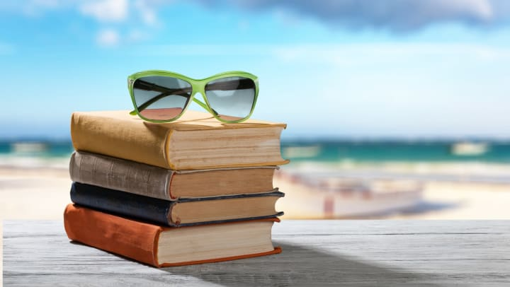 Stack of books with sunglasses on top sitting on a wood table with the beach and ocean blurred in the background.