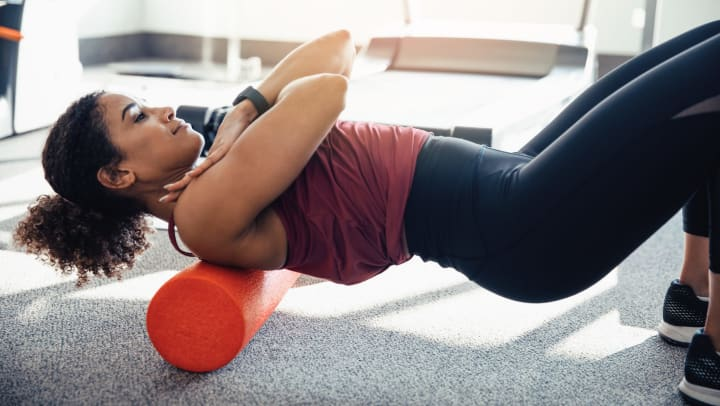 A young woman in workout clothes stretches her back on a foam roller at the gym.