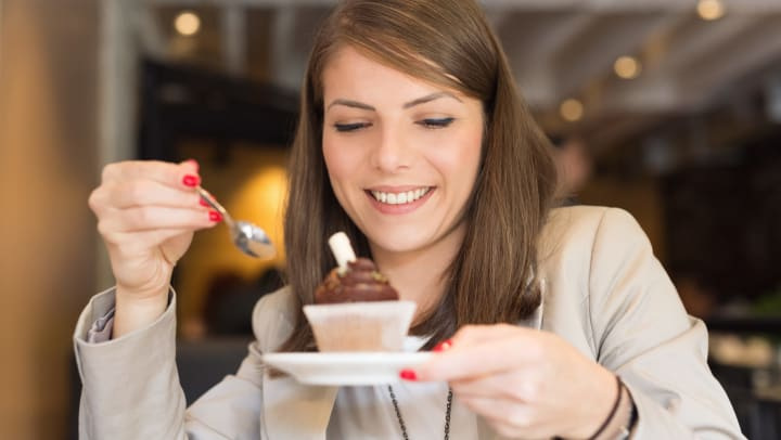 A woman smiling as she eats a cupcake with a spoon.
