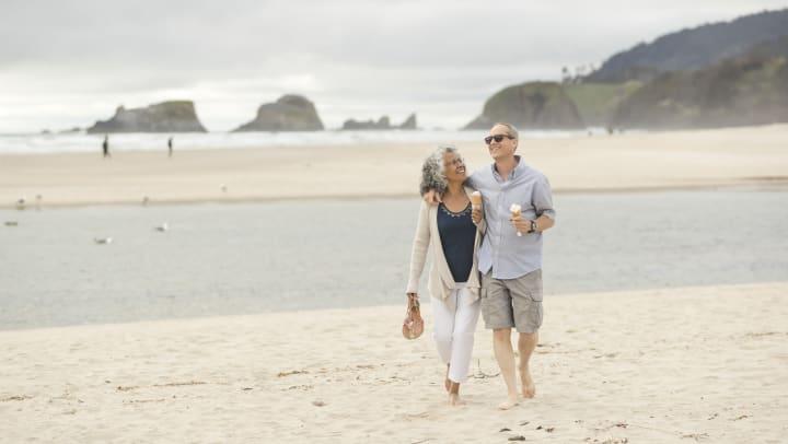 Elderly couple walking down the beach with ice cream cones.
